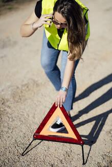 Woman having a breakdown posting warning triangle - OCMF01075