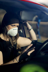 Woman in car wearing respirator mask using cell phone - OCMF01081