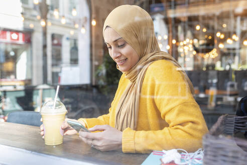 Portrait of young woman with smoothie and smartphone in a cafe - WPEF02714