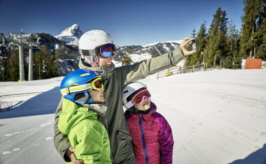 Mother with her children, taking a selfie on ski slope - DIKF00388