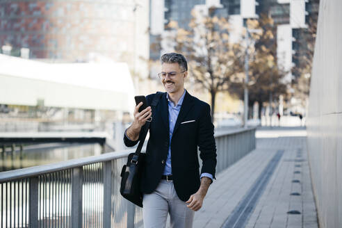 Smiling gray-haired businessman walking in the city using cell phone - JRFF04193