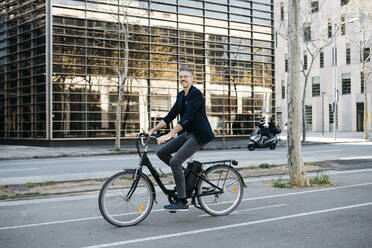 Gray-haired businessman riding on an electric bike through the city center - JRFF04226