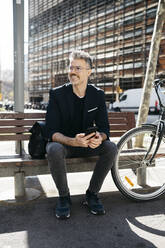 Gray-haired businessman sitting on a bench next to bicycle in the city - JRFF04229