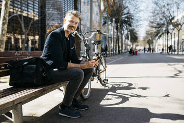 Portrait of gray-haired businessman sitting on a bench next to bicycle in the city - JRFF04232