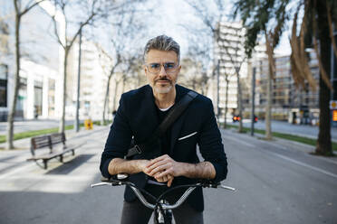 Portrait of a gray-haired businessman with bicycle in the city - JRFF04235