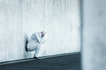 Despaired man wearing protective clothing leaning against concrete wall - WVF01509