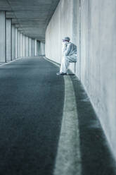 Exhausted man wearing protective clothing sitting in a niche of a concrete wall in a tunnel - WVF01512