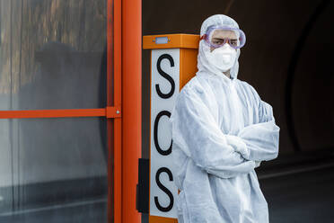 Portrait of man wearing protective clothing leaning against SOS telephone - WVF01515