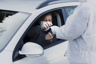 Man wearing protective clothing controlling senior man in car - WVF01518