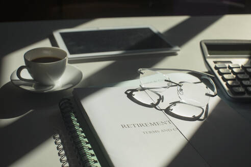 Retirement portfolio on sunny desk with coffee and eyeglasses - HOXF05319
