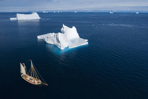 Ship sailing past icebergs on sunny blue ocean Greenland - HOXF05376
