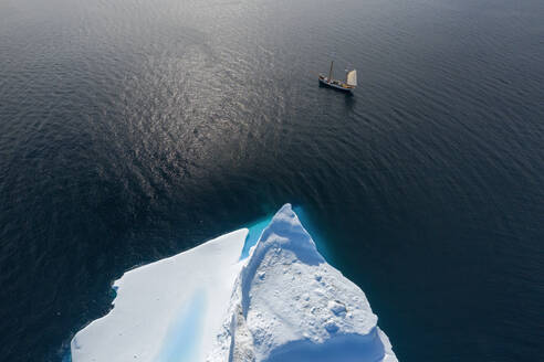 Drone point of view ship sailing past iceberg on sunny ocean Greenland - HOXF05382