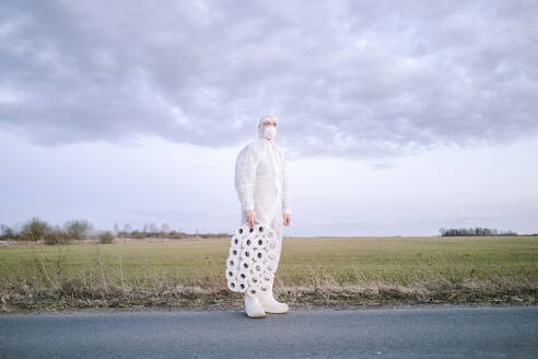 Man wearing protective suit and mask standing on country road with toilet rolls - EYAF00957