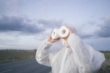 Man wearing protective suit and mask using toilet rolls like binoculars - EYAF00960