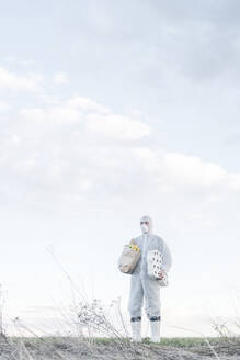 Man wearing protective suit and mask holding toilet rolls and grocery bag in the countryside - EYAF00963