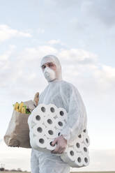 Man wearing protective suit and mask holding toilet rolls and grocery bag outdoors - EYAF00966