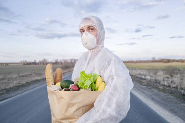 Man wearing protective suit and mask holding grocery bag on a country road - EYAF00969