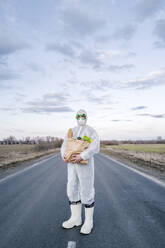 Man wearing protective suit and mask holding grocery bag on a country road - EYAF00972