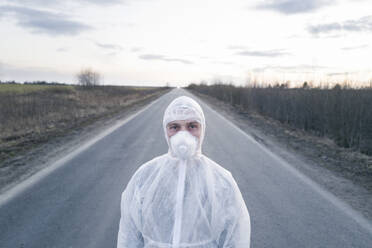 Portrait of man wearing protective suit and mask standing on country road - EYAF00978