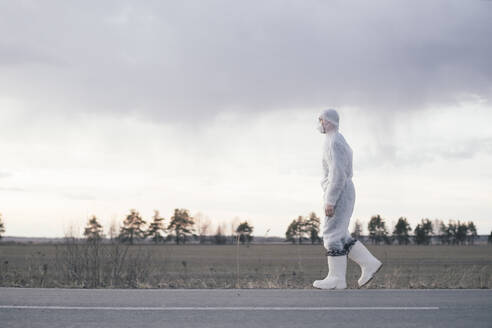 Man wearing protective suit and mask at the roadside of a country road - EYAF00981