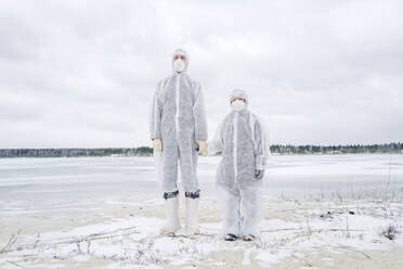 Father and son wearing protective suits standing at frozen river - EYAF00987