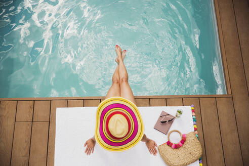 Woman in sun hat relaxing at summer poolside - HOXF05466