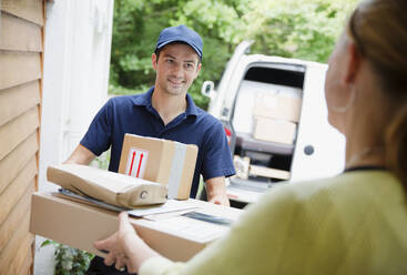 Deliveryman delivering packages to woman at front door - HOXF05523
