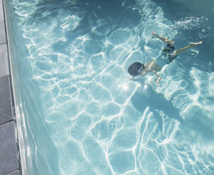 Boy swimming underwater in sunny, summer swimming pool - HOXF05526