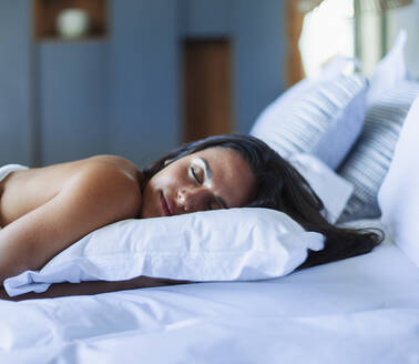 Serene young woman sleeping on pillow in bed - HOXF05556