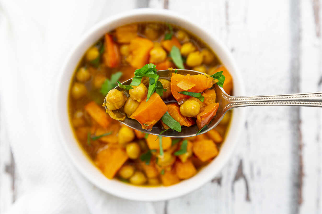 Spoon of oriental pumpkin stew with red kuri squash, roasted turmeric  chick-peas and parsley – Stockphoto