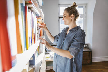 Pregnant woman standing at bookshelf at home - MFF05105