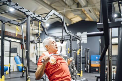 Senior man practising at cable machine in gym - OCMF01105