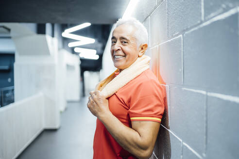 Portrait of smiling senior man having a break and leaning agianst a wall in gym - OCMF01114
