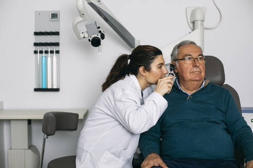 ENT physician examining ear of a senior man with an otoscope - ABZF03032