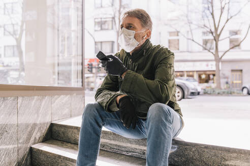 Man with mask sitting on stairs in the city holding smartphone - MFF05153