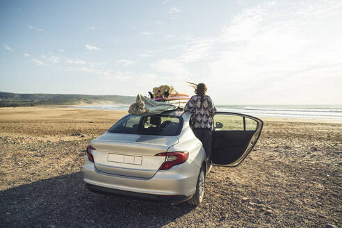Back view of woman with car on the beach looking to the sea, Tafedna, Morocco - HBIF00082