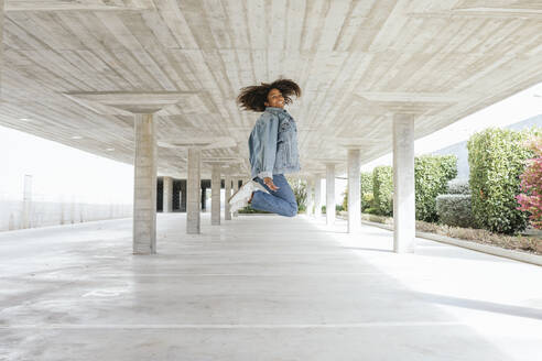 Smiling woman jumping in empty parking deck - TCEF00306