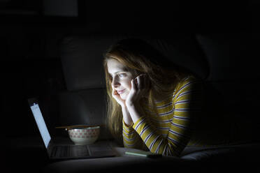Young woman lying on the couch at home using laptop - AFVF05782