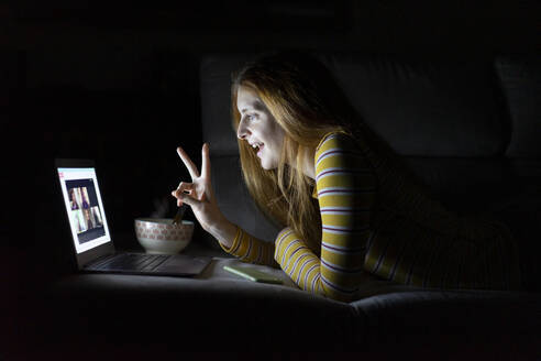 Young woman having a laptop video conference on the couch at home - AFVF05791
