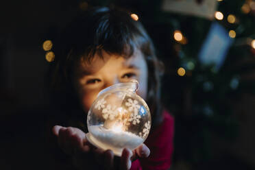 Little girl holding lighted glass ball at Christmas time - GEMF03498
