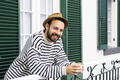 Portrait of smiling man standing on balcony - AFVF05802