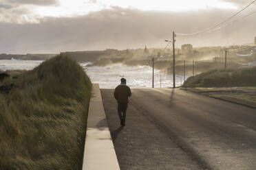 Rear view of man walking on a road at the coast, Sao Miguel Island, Azores, Portugal - AFVF05808