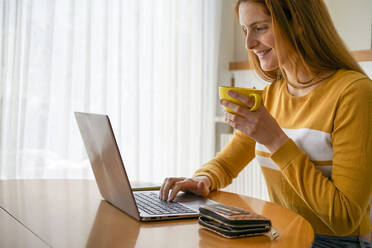 Smiling young woman with cup of coffee using laptop at home - AFVF05826