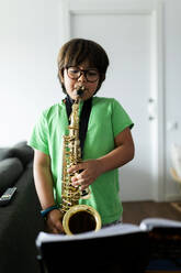 Boy exercising to play the saxophone at home - VABF02677