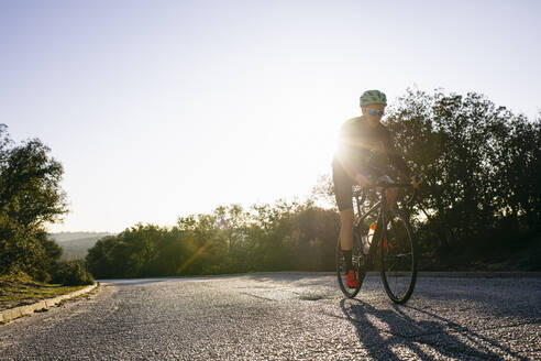 Athlete riding bicycle on country road at sunset - ABZF03073