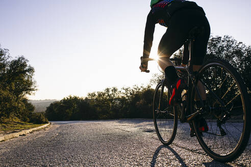 Close-up of athlete riding bicycle on country road at sunset - ABZF03076
