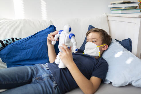 Boy with mask playing in his room during the corona crisis with his new, only friend, a robot - HMEF00826