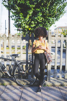 Young woman with afro hairdo using smartphone in the city - MEUF00212