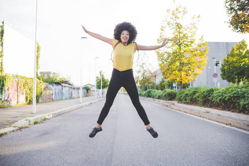 Happy young woman with afro hairdo jumping on a street in the city - MEUF00224