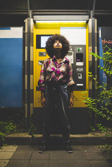 Young woman with afro hairdo standing at ticket machine at night looking up - MEUF00272